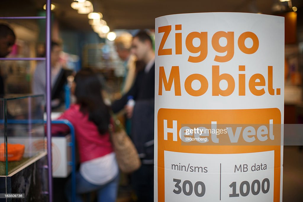 A sign advertises a Ziggo mobile communications package deal as customers browse inside a Ziggo NV store in Utrecht, Netherlands, on Friday, Oct. 4, 2013. Cable-TV provider Ziggo, which is 28.5 percent owned by Liberty Global Plc, is pushing into the Dutch mobile market with low-priced packages, following a playbook pioneered by French discount operator Iliad SA. Photographer: Jasper Juinen/Bloomberg via Getty Images