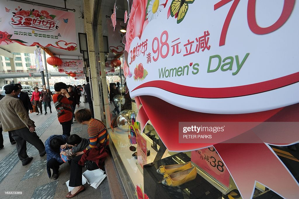 A sign advertises discounts for International Women's Day in a store in Shanghai on March 8, 2013. International Women's Day in China is celebrated with various events including discount shopping for women at malls in cities around China. Peter PARKS