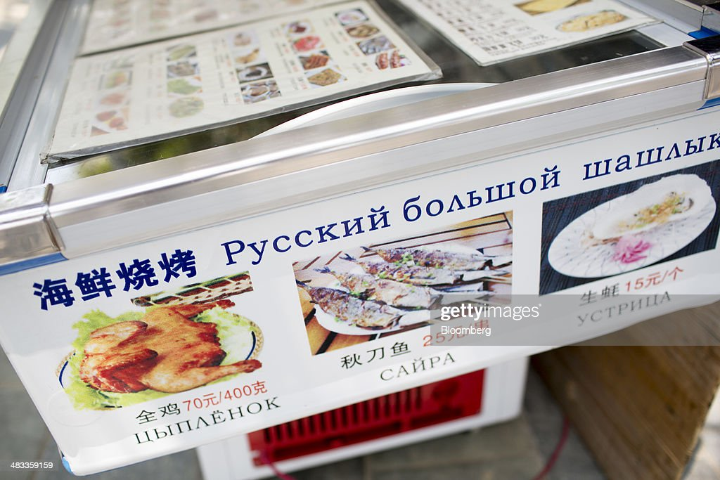 A sign advertises food in Russian and Chinese at a restaurant in the Dadonghai district of Sanya, Hainan Province, China, on Monday, April 7, 2014. The yuan is poised to recover from declines that have made it Asia's worst-performing currency as China seeks to prevent an exodus of capital that would threaten economic growth, according to the most accurate forecasters. Photographer: Brent Lewin/Bloomberg via Getty Images