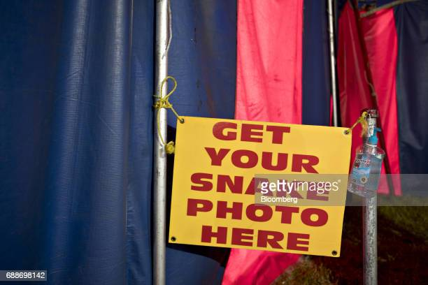 A sign advertises having a photo taken with a snake in the World of Wonders tent during the Dreamland Amusements carnival in the parking lot of the...