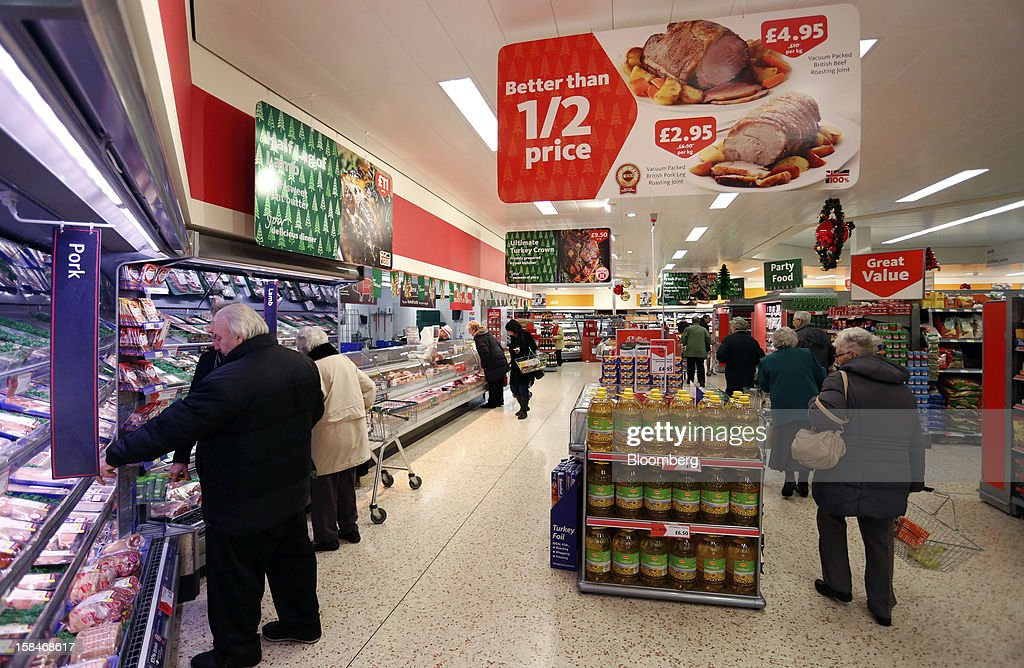 A sign advertising 'Better than 1/2 price' hangs from the ceiling in the chilled meat section of a Morrisons supermarket, operated by William Morrisons Supermarkets Plc, in Chadderton, U.K., on Monday, Dec. 17, 2012. The British Christmas is the biggest epicurean occasion of the year, with households spending a total of 4 billion pounds on food in the final week before Dec. 25. Photographer: Paul Thomas/Bloomberg via Getty Images