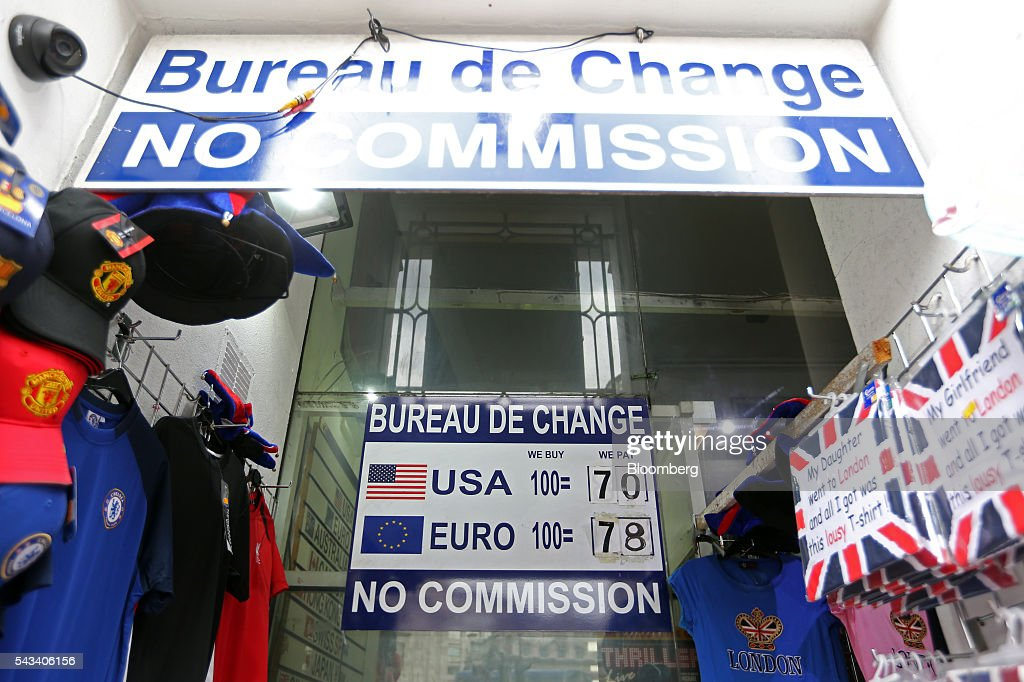 A sign advertising exchange rates for U.S. dollars and euros hangs outside a foreign currency exchange bureau in London, U.K., on Tuesday, June 28, 2016. The pound rose for the first time since the U.K.s vote to leave the European Union, as a recovery in investor appetite for higher-yielding assets seeped through currency markets. Photographer: Chris Ratcliffe/Bloomberg via Getty Images