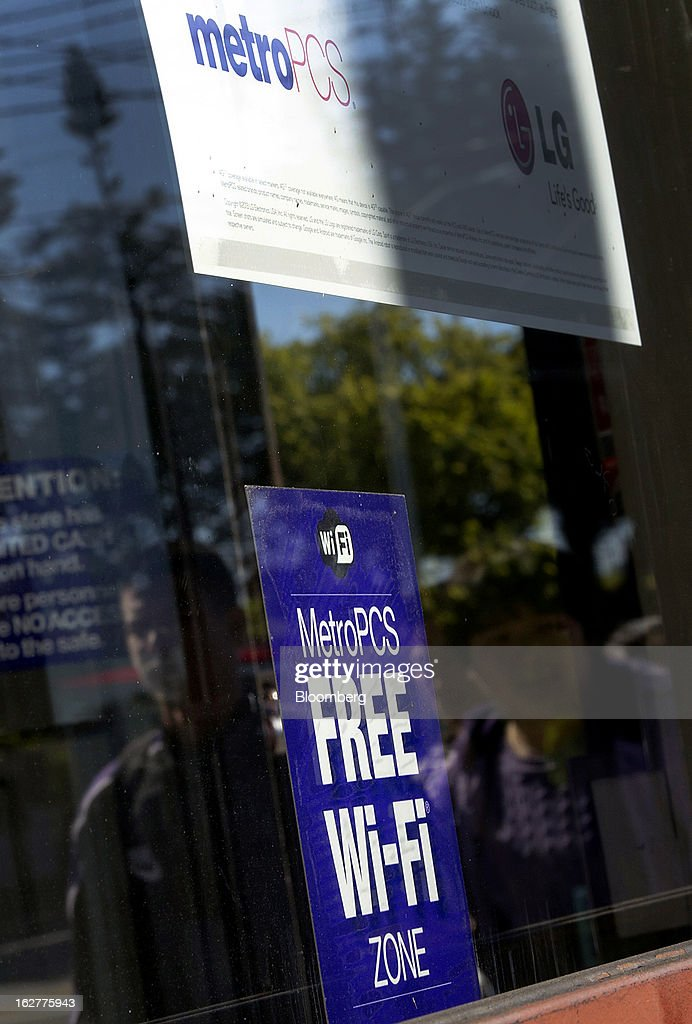 A sign advertising free wi-fi is displayed as reflections of pedestrians are seen in the window of a MetroPCS Communications Inc. store in San Francisco, California, U.S., on Tuesday, Feb. 26, 2013. MetroPCS Communications Inc. fourth-quarter revenue, released today, matches estimated earnings. Photographer: David Paul Morris/Bloomberg via Getty Images