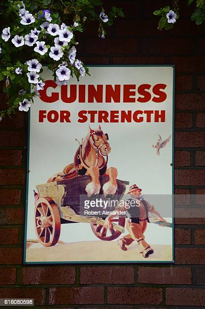 A sign advertising Guinness stout is mounted on the exterior wall of a pub in Dublin Ireland