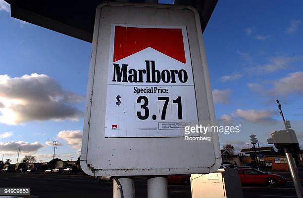 A sign advertising Marlboro brand cigarettes hangs from a post at a San Diego California service station on Sunday morning January 25 2004 Altria...