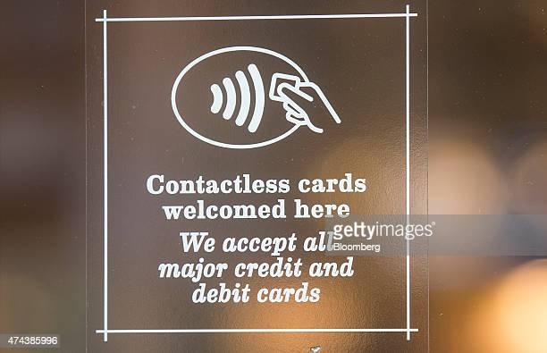 A sign advertising the acceptance of contactless payment sits in the window of a Wasabi sushi restaurant in London UK on Friday May 22 2015 Credit...