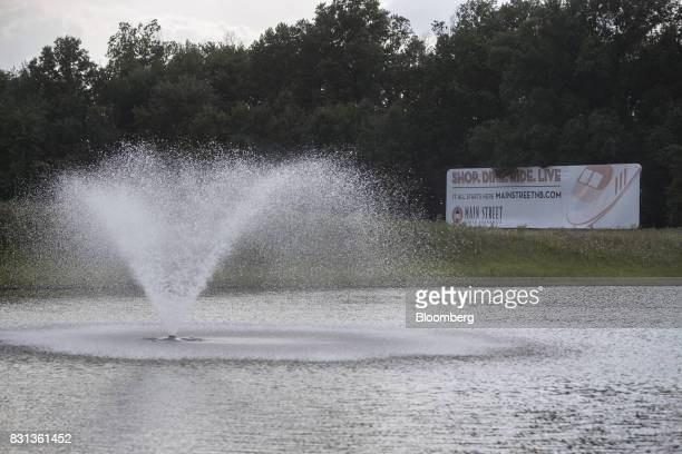 A sign advertising the Main Street North Brunswick development project reads 'Shop Dine Ride Live' next to a pond in North Brunswick New Jersey US on...
