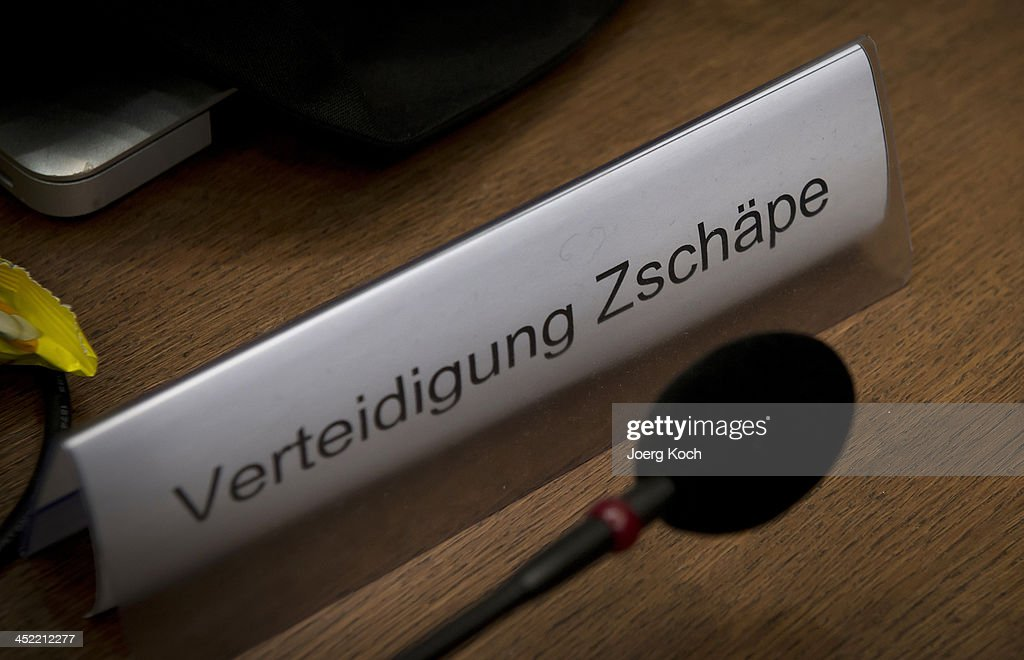 A sign and a microphone sit on the table of co-defendant Beate Zschaepe as she prepares for today's NSU neo-Nazi murders trial on November 27, 2013 in Munich, Germany. Among those scheduled to testify in NSU murder trial today is the mother of Beate Zschaepe. Zschaepe is accused of assisting neo-Nazis Uwe Mundlos and Uwe Boehnhardt in their eight-year murder spree that targeted nine immigrants and one policewoman.