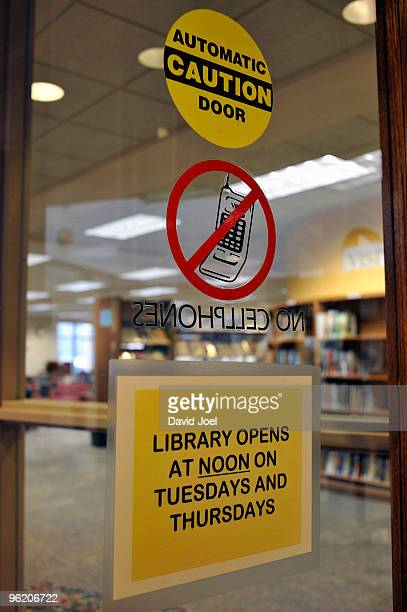 Sign announcing cutbacks in library hours