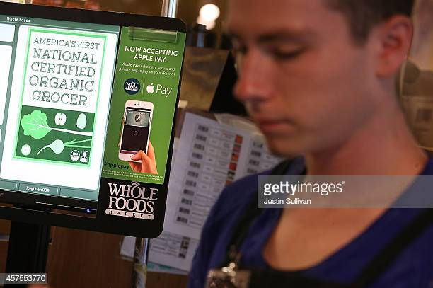 A sign announcing that Whole Foods is accepting Apple Pay is posted on a cash register at a Whole Foods store on October 20 2014 in San Francisco...