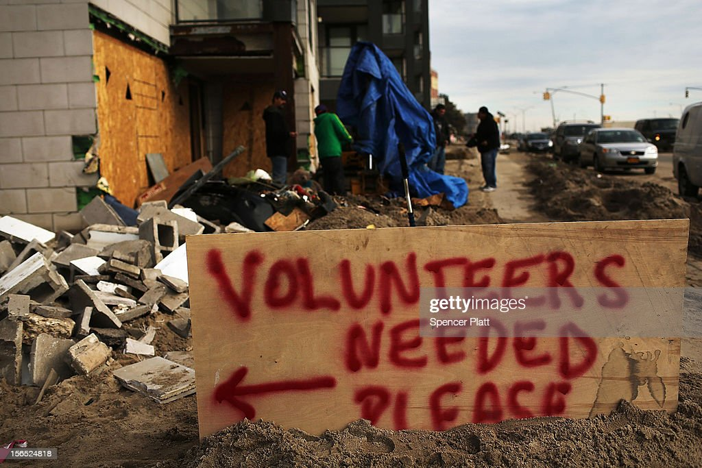 A sign asks for volunteers in the clean-up effort in the heavily damaged Rockaway neighborhood where a large section of the iconic boardwalk was washed away on November 16, 2012 in the Queens borough of New York City. Over two weeks after Superstorm Sandy slammed into parts of New York and New Jersey, thousands are still without power and heat.