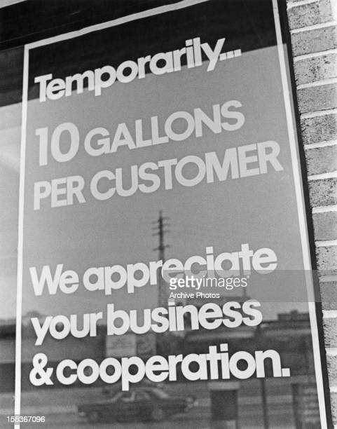 A sign at a petrol station announcing temporary fuel rationing USA circa 1974 The sign reads 'Temporarily10 gallons per customer We appreciate your...