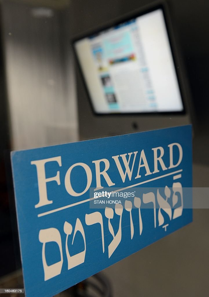 A sign at the front door of the Forward office is seen with a computer monitor showing the newspaper website February 1, 2013 in the Lower Manhattan section of New York. A redesigned Yiddish website, part of the 115-year old Jewish newspaper, will be launched on February 4. AFP PHOTO/Stan HONDA