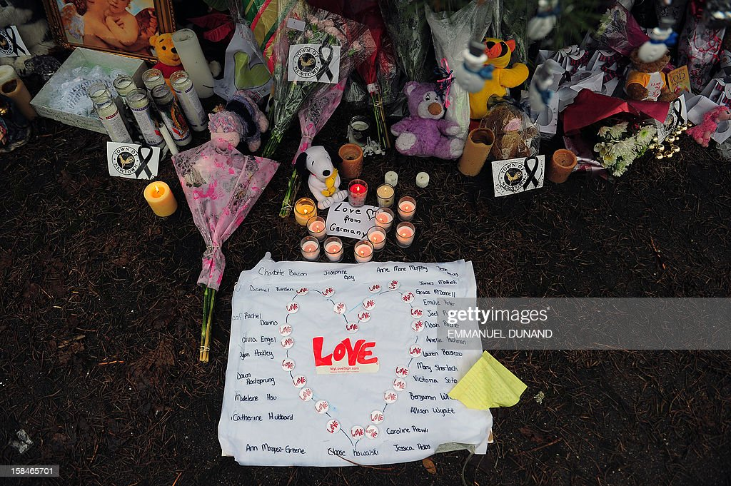 A sign bears the names of the victims of an elementary school shooting at a makeshift shrine to the victims of an elementary school shooting in Newtown, Connecticut, December 17, 2012. Funerals began Monday in the little Connecticut town of Newtown after the school massacre that took the lives of 20 small children and six staff, triggering new momentum for a change to America's gun culture. The first burials, held under raw, wet skies, were for two six-year-old boys who were among those shot in Sandy Hook Elementary School. On Tuesday, the first of the girls, also aged six, was due to be laid to rest. There were no Monday classes at all across Newtown, and the blood-soaked elementary school was to remain a closed crime scene indefinitely, authorities said. AFP PHOTO/Emmanuel DUNAND
