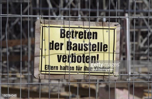 Sign ' Betreten der Baustelle verboten Eltern haften fuer Ihre Kinder ' behind a hoarding