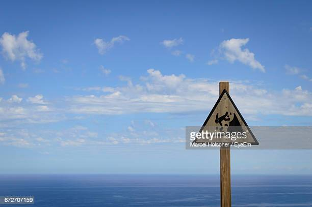 Sign Board Against Sea And Sky
