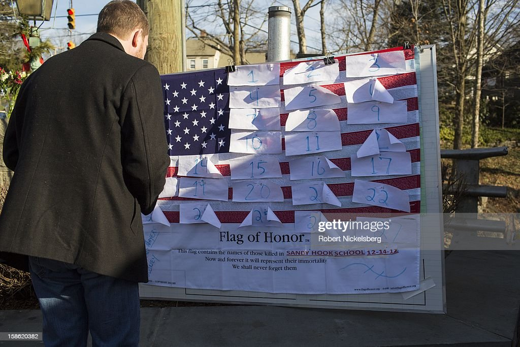A sign board displays 27 pieces of paper December 15, 2012 representing the 20 children and 7 adults killed by a gunman the previous day in Sandy Hook, Connecticut.
