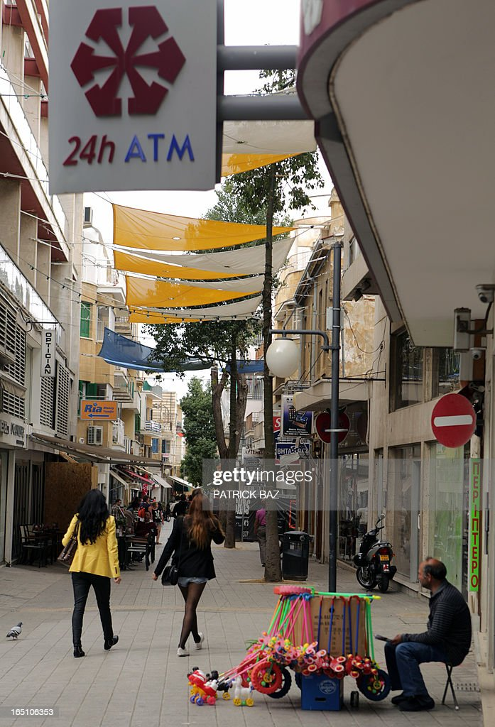 A sign board indicating an ATM of a Laiki bank branch is seen in front of women walking past a street vendor on March 30, 2013 in Nicosia. Big savers in Cyprus's largest bank face losses of up to 60 percent, far greater than originally feared under the island's controversial EU-led bailout plan, officials said on March 30.