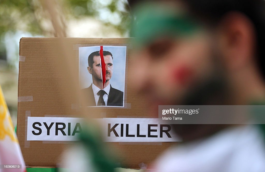 A sign denouncing Bashar Assad, President of Syria, is displayed at a rally of groups opposing Iranian President Ahmadinejad's speech at the United Nations General Assembly on September 26, 2012 in New York City. Politicians including former New York Mayor Rudolph Giuliani, former House Speaker Newt Gingrich, former Homeland Security Secretary Tom Ridge, former New Mexico Governor Bill Richardson and former U.N Ambassador John Bolton spoke at the pro-democracy rally which also included Syrian pro-democracy protesters.