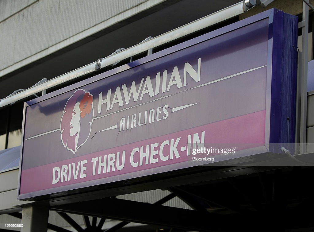 A sign directing travelers to drive thru check-in at Hawaiian Airlines Inc. is displayed at an airport in Honolulu, Hawaii, U.S., on Wednesday, Jan. 9, 2013. Honolulu, the southernmost major U.S. city, is a major financial center of the islands of the Pacific Ocean. Photographer: Tim Rue/Bloomberg via Getty Images