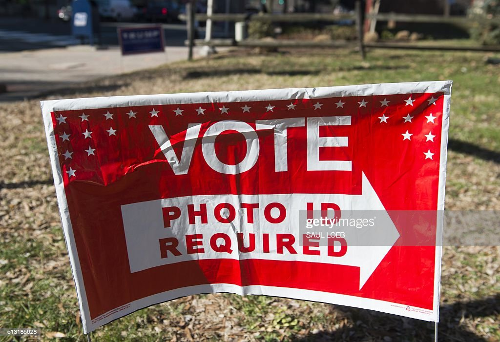 A sign directing voters where to vote is seen during the Super Tuesday primary voting at a polling place located at Fire Station in Arlington...