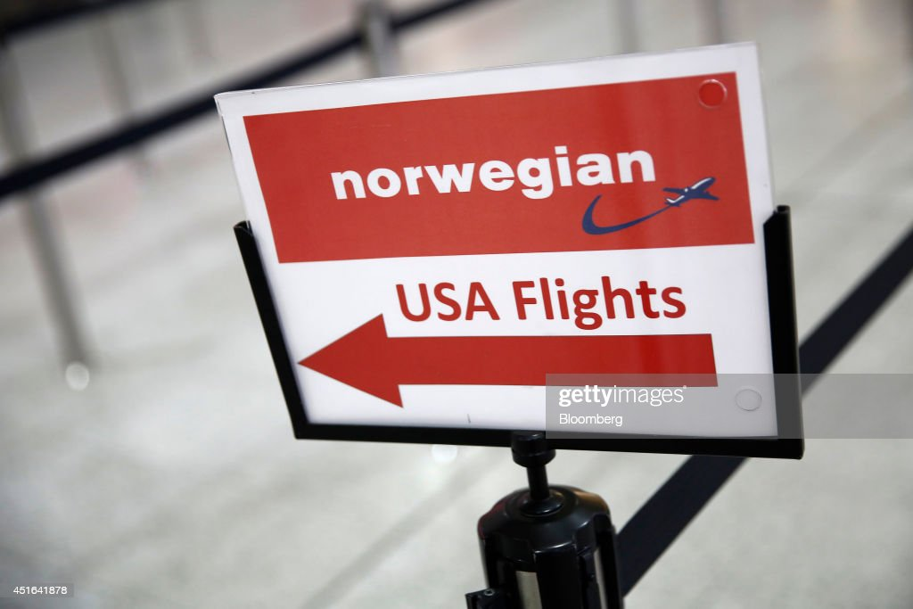 A sign directs passengers to Norwegian Air Shuttle AS's checkin desk ahead of the company's inaugural flight to New York at the south terminal of...