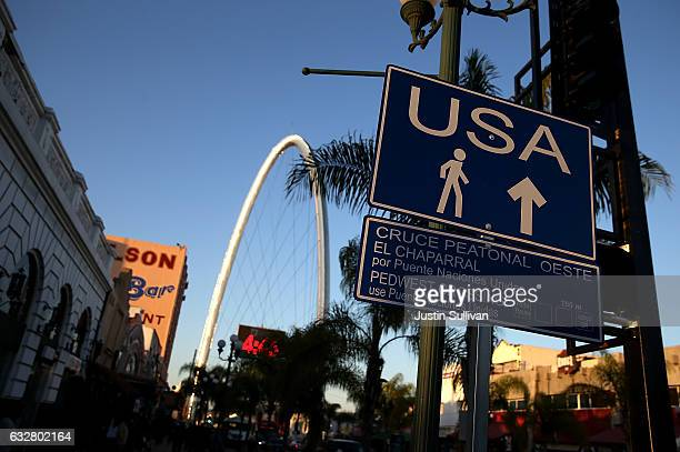 A sign directs pedestrians to the US border crossing on January 26 2017 in Tijuana Baja California US President Donald Trump announced a proposal to...
