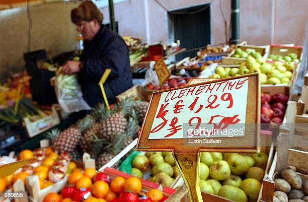 A sign displays prices for fruit in the Italian Lire and the new Euro January 3 2002 at the Rialto outdoor market in Venice Italy The Euro went into...