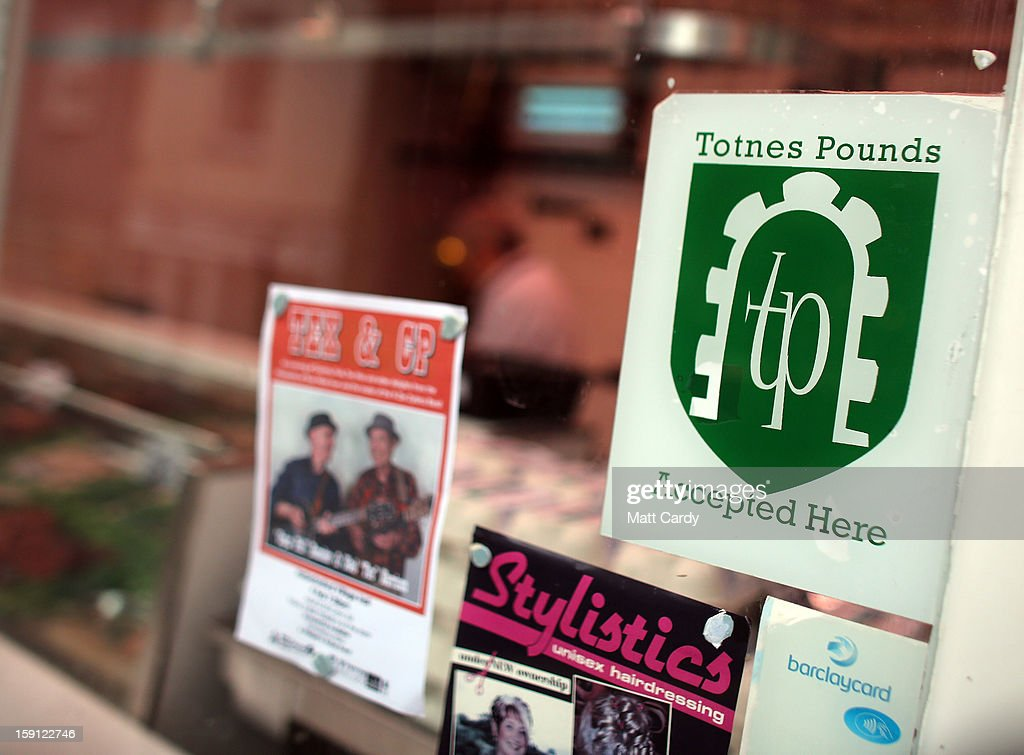 A sign encouraging people to use Totnes pounds is seen in a shop window along the main shopping street of Totnes on January 8, 2013 in Totnes, England. The Devon town is renowned for its belief in promoting trade of local independent retailers, famously denying the plans by national coffee chain Costa to open a high street branch in the town. Boasting its own local currency, Totnes has a shop vacancy rate of 6%, less than half than the national average, whilst 80% of outlets are independently owned.