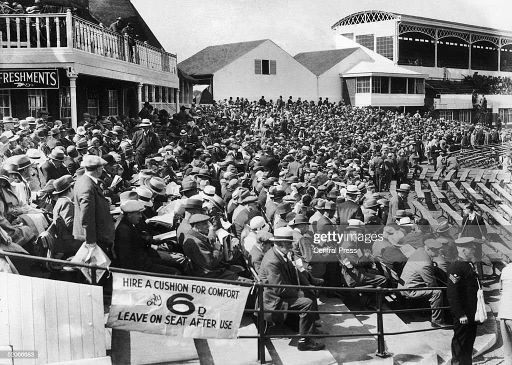A sign exhorts spectators to 'Hire a Cushion for Comfort Only 6d' during the England V Australia test match at Headingley 1930