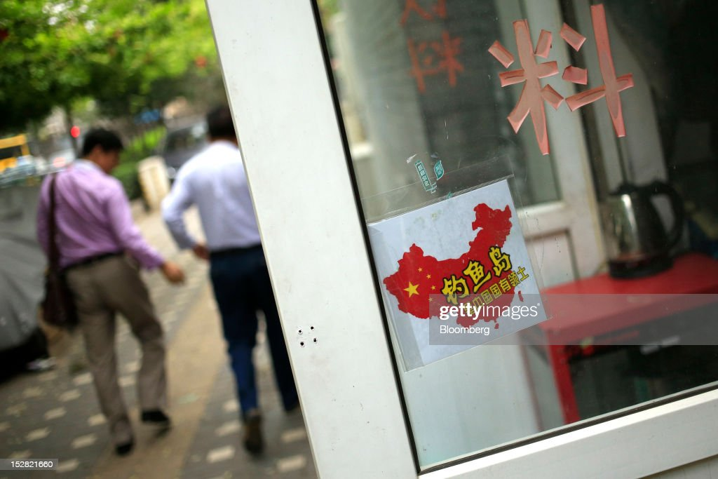A sign featuring the Chinese flag and the Chinese characters for 'Diaoyu Islands' is displayed on the door of a store in Beijing China on Thursday...