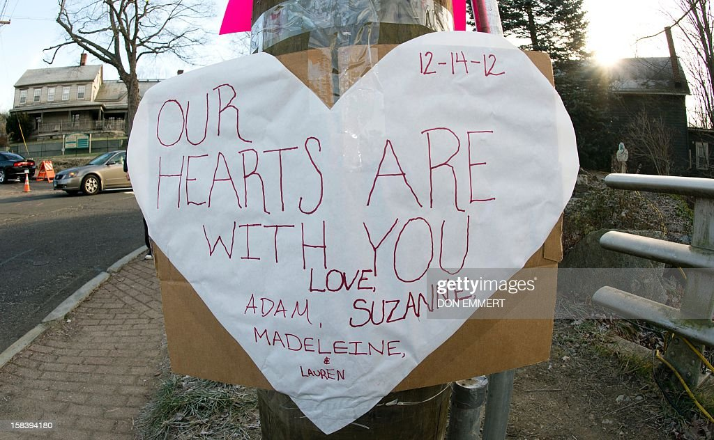 A sign fir the victims of the Sandy Hook Elementary School shooting is seen on a telephone pole in the business area of Newtown, Connecticut, on December 15, 2012. The residents of an idyllic Connecticut town were reeling in horror from the massacre of 20 small children and six adults in one of the worst school shootings in US history. The heavily armed gunman shot dead 18 children inside Sandy Hook Elementary School, said Connecticut State Police spokesman Lieutenant Paul Vance. Two more died of their wounds in hospital.