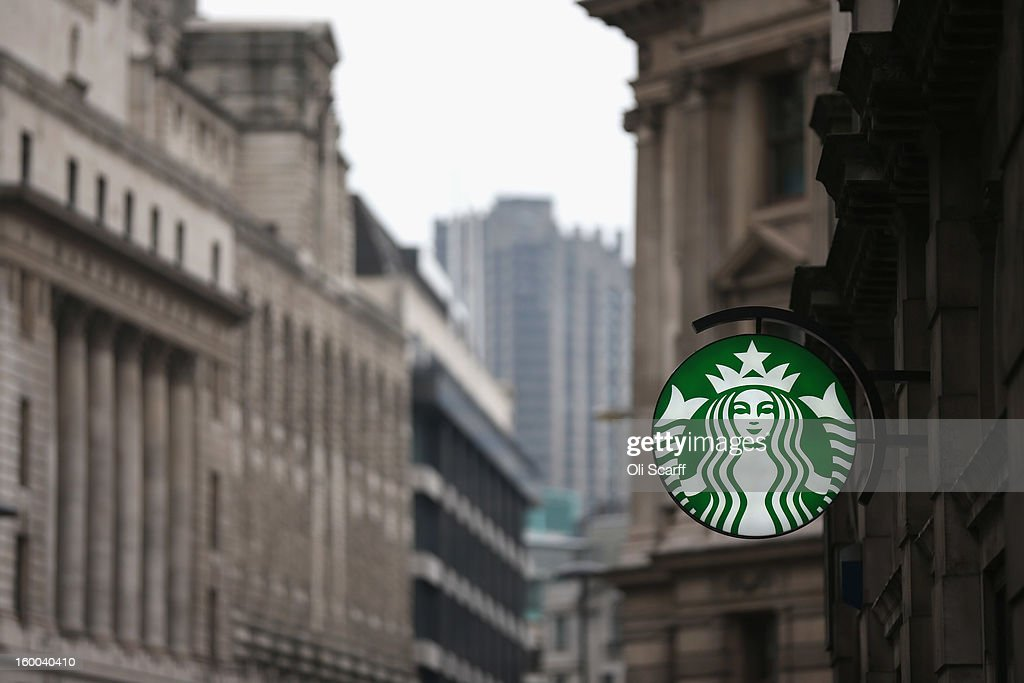 A sign for a branch of Starbucks coffee is illuminated at dusk in the City of London on January 25, 2013 in London, England. .