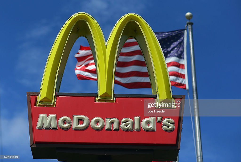 A sign for a McDonald's restaurant sits in front of an American Flag July 23 2012 in Miami Florida The company announced that 2nd quarter profit...