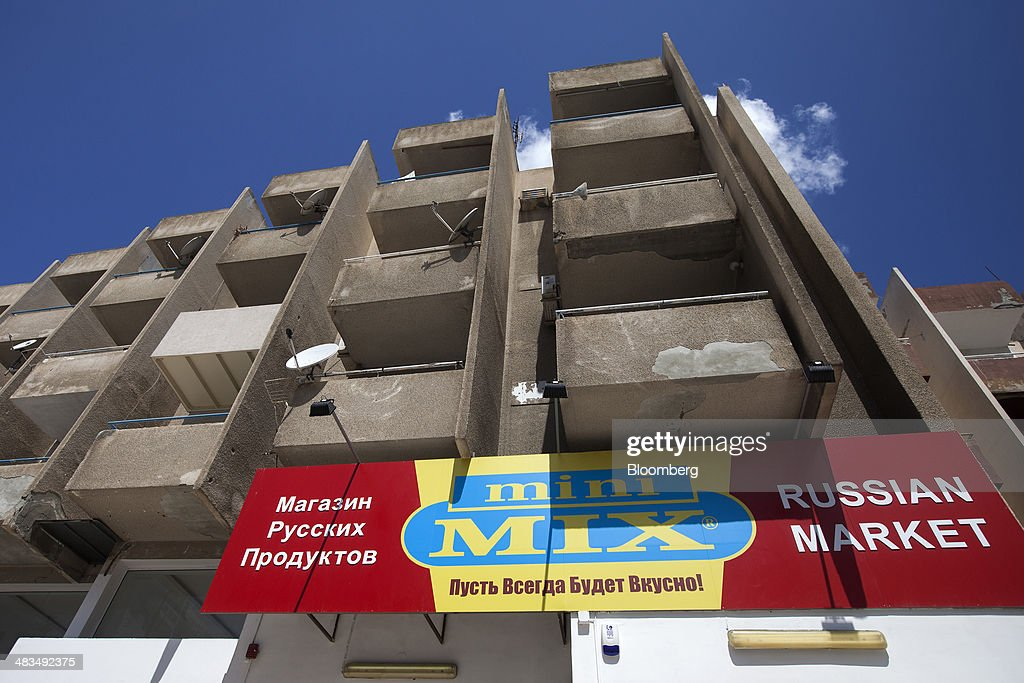 A sign for a Mini-Mix Russian supermarket sits on display below an apartment block in Limassol, Cyprus, on Tuesday, April 8, 2014. Cyprus wants to shield financial flows with Russia, where it's the biggest foreign investor, as the U.S. and the European Union ratchet up sanctions in response to President Vladimir Putin's annexing Crimea from Ukraine. Photographer: Andrew Caballero-Reynolds/Bloomberg via Getty Images
