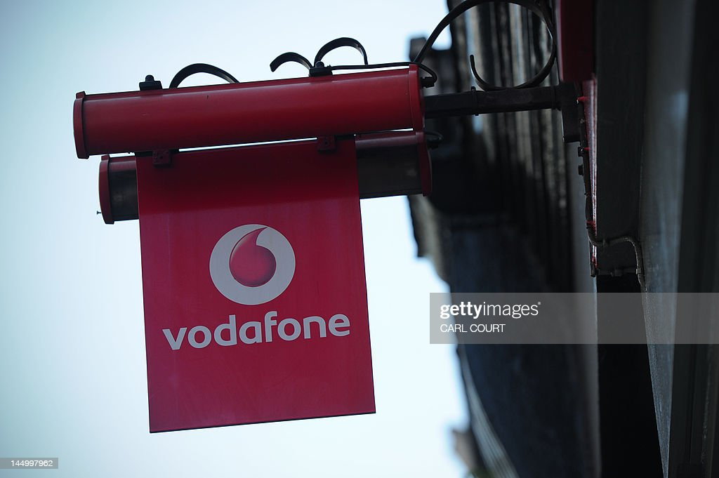 A sign for a Vodafone store is pictured in central London on May 22, 2012. British mobile phone giant Vodafone on Tuesday said annual net profits dropped almost 13 percent as eurozone losses offset asset sale gains and strong performances in emerging markets and the US. Vodafone said profit after tax hit £6.957 billion (8.6 billion euros, $11.0 billion) in the 12 months to March 31, down 12.7 percent compared with 2010/11. Revenue rose 1.2 percent to £46.4 billion in 2011/12. AFP PHOTO / CARL COURT