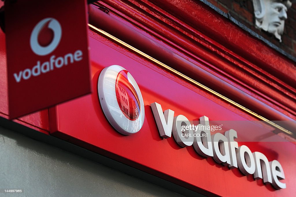 A sign for a Vodafone store is pictured in central London on May 22, 2012. British mobile phone giant Vodafone on Tuesday said annual net profits dropped almost 13 percent as eurozone losses offset asset sale gains and strong performances in emerging markets and the US. Vodafone said profit after tax hit £6.957 billion (8.6 billion euros, $11.0 billion) in the 12 months to March 31, down 12.7 percent compared with 2010/11. Revenue rose 1.2 percent to £46.4 billion in 2011/12.