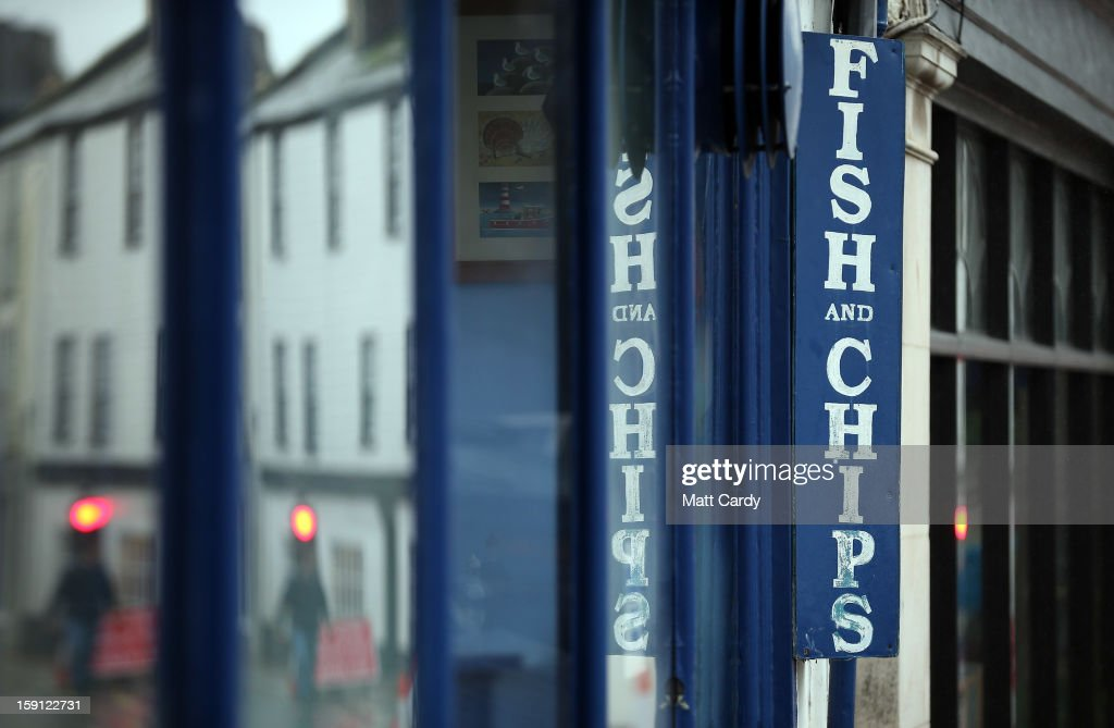 A sign for fish and chips is seen outside a shop along the main shopping street of Totnes on January 8, 2013 in Totnes, England. The Devon town is renowned for its belief in promoting trade of local independent retailers, famously denying the plans by national coffee chain Costa to open a high street branch in the town. Boasting its own local currency, Totnes has a shop vacancy rate of 6%, less than half than the national average, whilst 80% of outlets are independently owned.