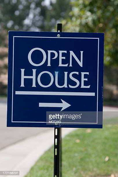 Sign for open house with right pointing arrow on green grass