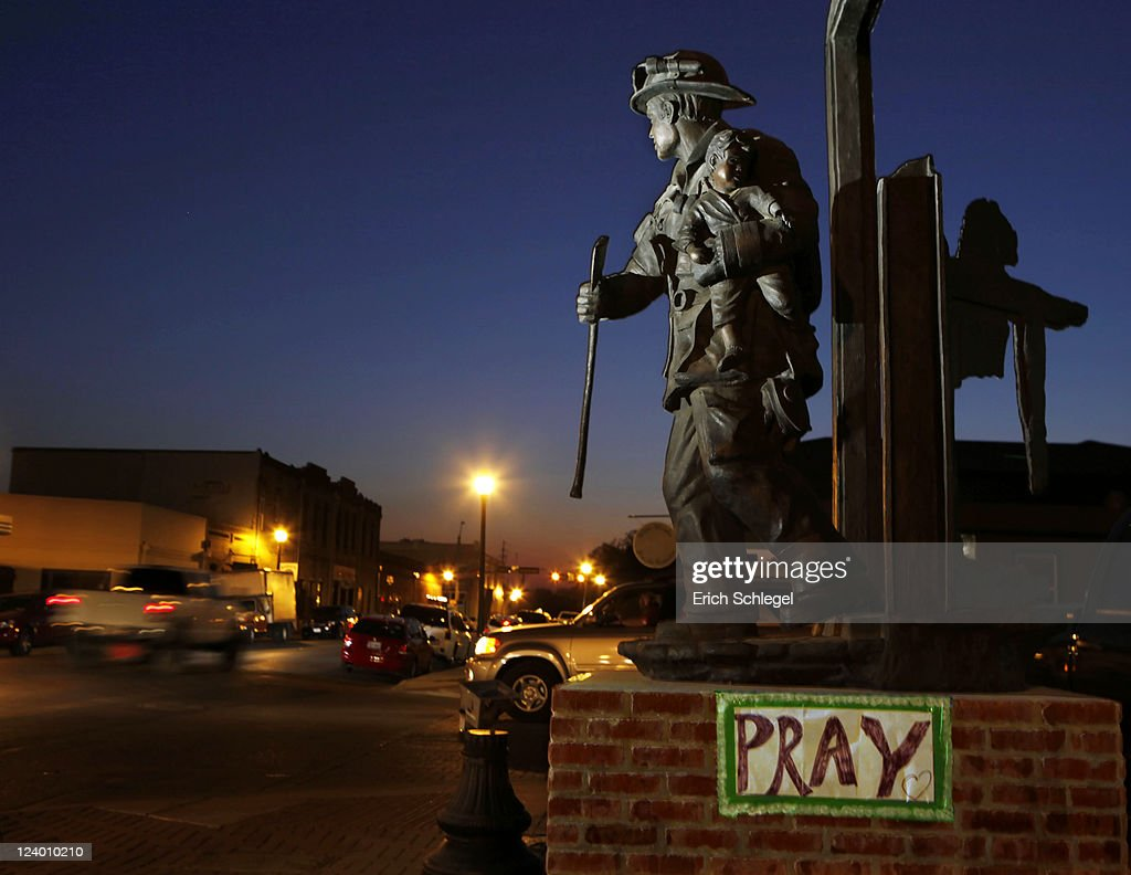A sign for prayer is taped to the base of the fireman's statue in front of the Bastrop Volunteer Fire Department September 7, 2011 in historic downtown Bastrop, Texas. Several large wildfires have been devastating Bastrop County for the last three days, but are now 30 percent contained, according to the Texas Forest Service.