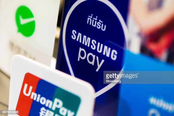 A sign for Samsung Electronics Co's Samsung pay is displayed among other payment methods at a store in Bangkok Thailand on Thursday Sept 28 2017...
