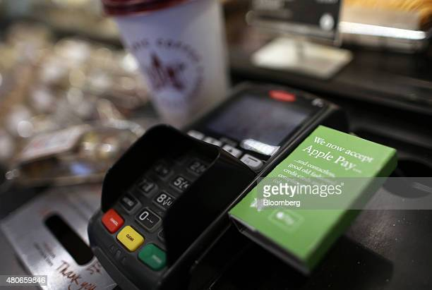 A sign for the launch of the Apple Pay system by Apple Inc is seen on the side of a payment device at a Pret A Manger Ltd store in this arranged...
