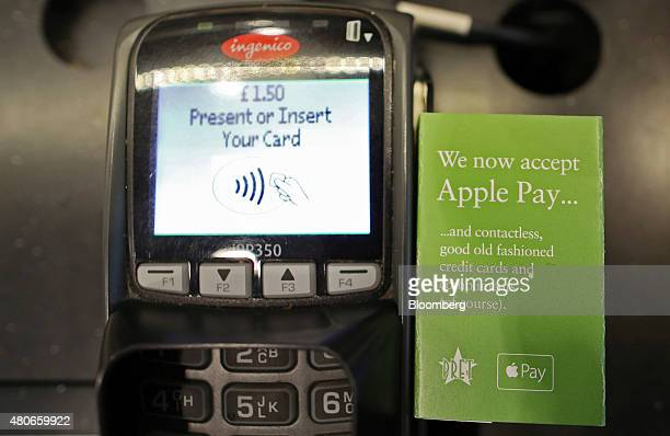 A sign for the launch of the Apple Pay system by Apple Inc is seen on the side of a payment device at a Pret A Manger Ltd store in London UK on...