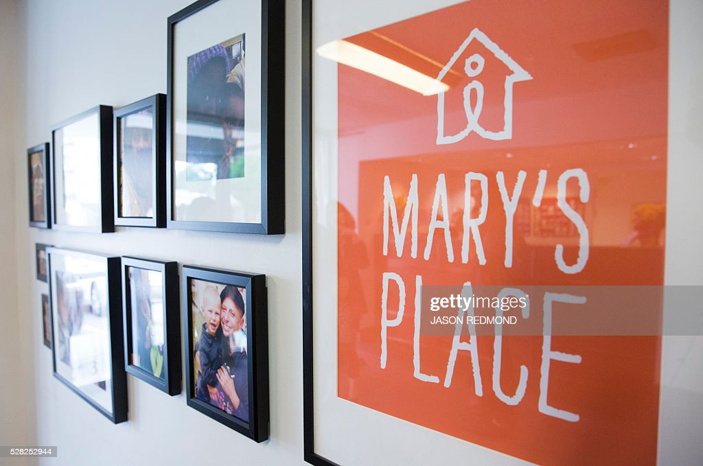 A sign for the non profit Mary's Place is pictured next to photos in a building owned by Amazon that is being used as a temporary homeless shelter for women and their families in Seattle, Washington on May 4, 2016. According to the non profit, Marys Place is a temporary emergency family nightshelter housing up to 60 families each night, including pets. Mary's place helps homeless women, children and families to reclaim their lives by providing shelter, nourishment, resources, healing and hope in a safe community. / AFP / Jason Redmond