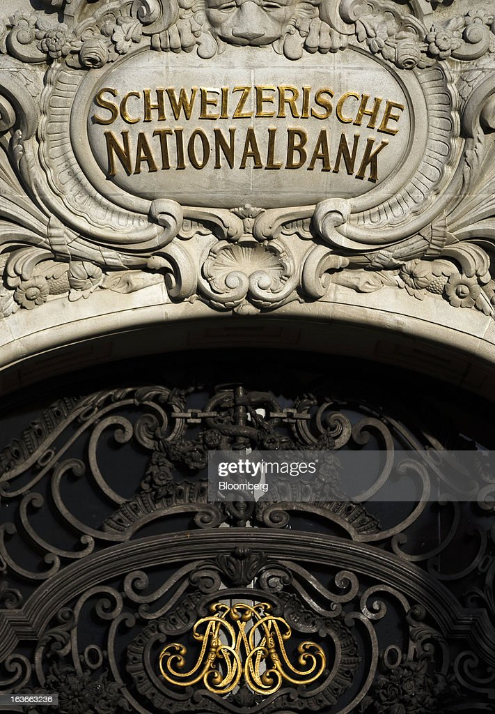 A sign for the Swiss National Bank (SNB), Switzerland's central bank, sits above the entrance to the building in Bern, Switzerland, on Tuesday, March 12, 2013. The Swiss central bank pledged to keep up its defense of the franc cap after almost doubling its currency holdings to shield the country from the fallout caused by the euro zone's crisis. Photographer: Valentin Flauraud/Bloomberg via Getty Images