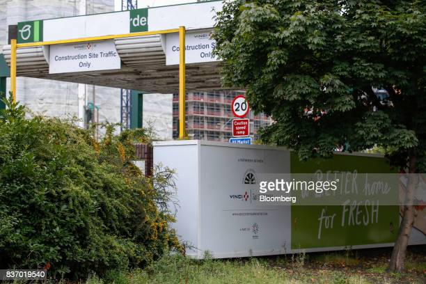 A sign for Vinci SA and St Modwen Properties Plc stands outside the Nine Elms Square construction site in London UK on Tuesday Aug 22 2017...