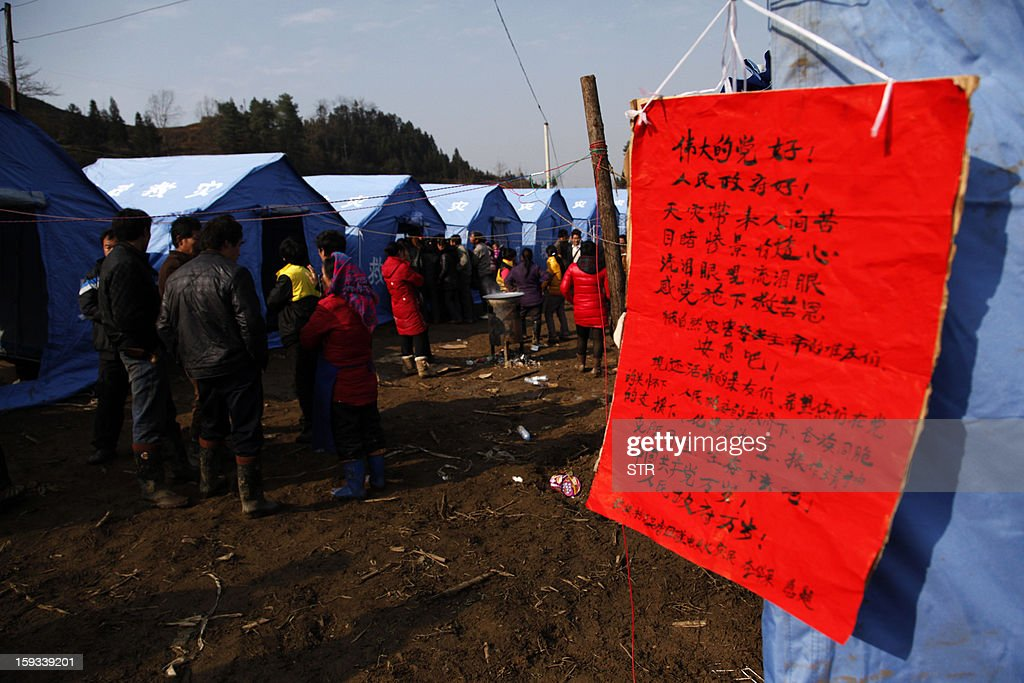 A sign from residents thanking the the Communist Party of China (CPC) (R) is displayed on a temporary tent after the rescue mission is finished in the disaster-hit area in Gaopo village, southwest China's Yunnan province on January 12, 2013. Three people remain missing after a landslide which killed 43, including seven from a single family, struck a remote village in southwestern China, state media said on January 12. CHINA