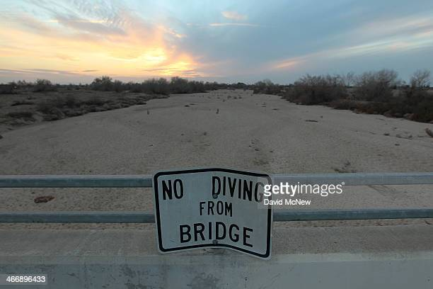 A sign from wetter times warns people not to dive from a bridge over the Kern River which has been dried up by water diversion projects and little...
