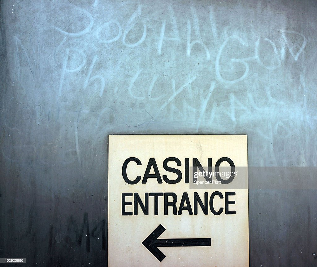 A sign guides people to a casino along the boardwalk in Atlantic City on July 29, 2014 in Atlantic City, New Jersey. Since January of 2014, four of Atlantic City's 11 casinos have announced plans to close, gone bankrupt or closed leaving thousands of residents without jobs. As neighboring cities open gambling businesses, fewer people are traveling to Atlantic City for visits to casinos. Since 2006 Casino revenue in Atlantic City has fallen from $5.6 billion to $2.86 billion. Experts believe this is the biggest crisis Atlantic City has faced in its 36 year relationship with gambling.