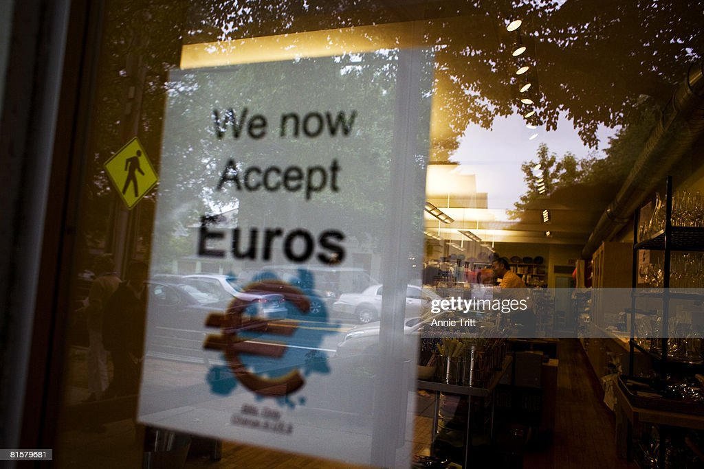 A sign hanging in the window of Loaves & Fishes Cookshop indicates that, like several Hampton retailers, they have begun accepting Euros as payment, catering to the large amounts of visiting Europeans and the weak dollar, June 15, 2008 in Bridgehampton, in the Hamptons section of Long Island, New York. This is the first year they are doing so.